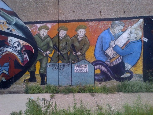 Part of a mural painted on the south side of the viaduct at 16th and Western in Pilsen (Chicago). Depicts Reagan (representing US) and Chernenko(?) (representing USSR) as a 2-headed snake fighting over an ICBM as a firing squad shoots a school and an unemployment office.